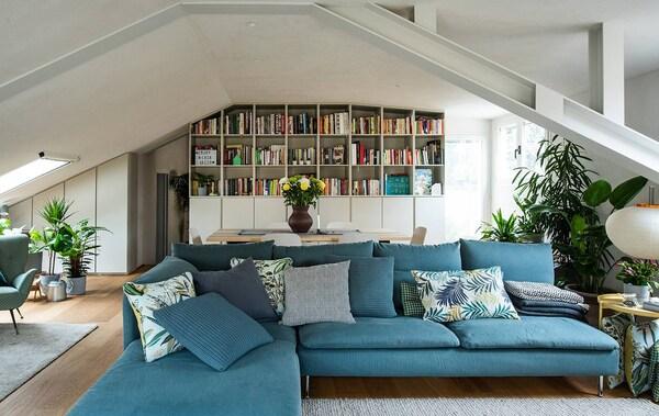 Il soggiorno con divano in primo piano e tavolo e libreria di fondo