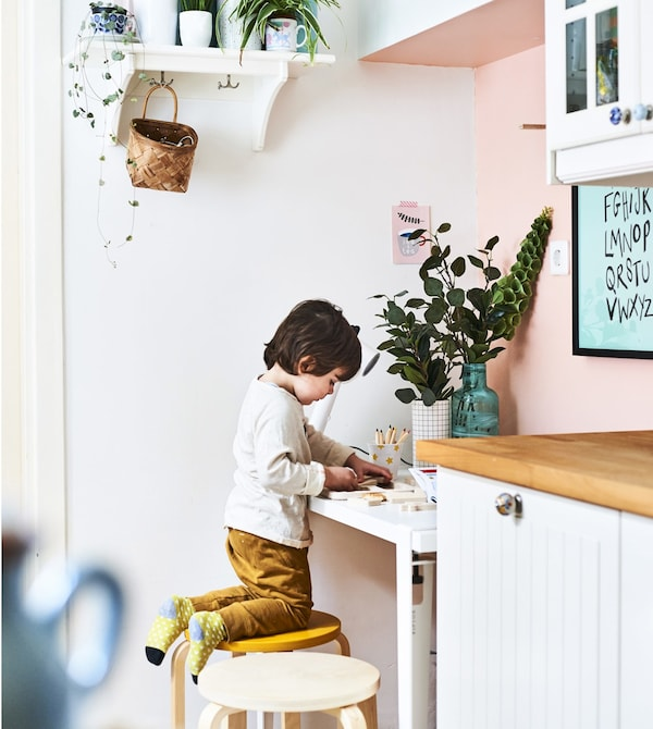 Ilaria's son drawing at a desk in the kitchen.