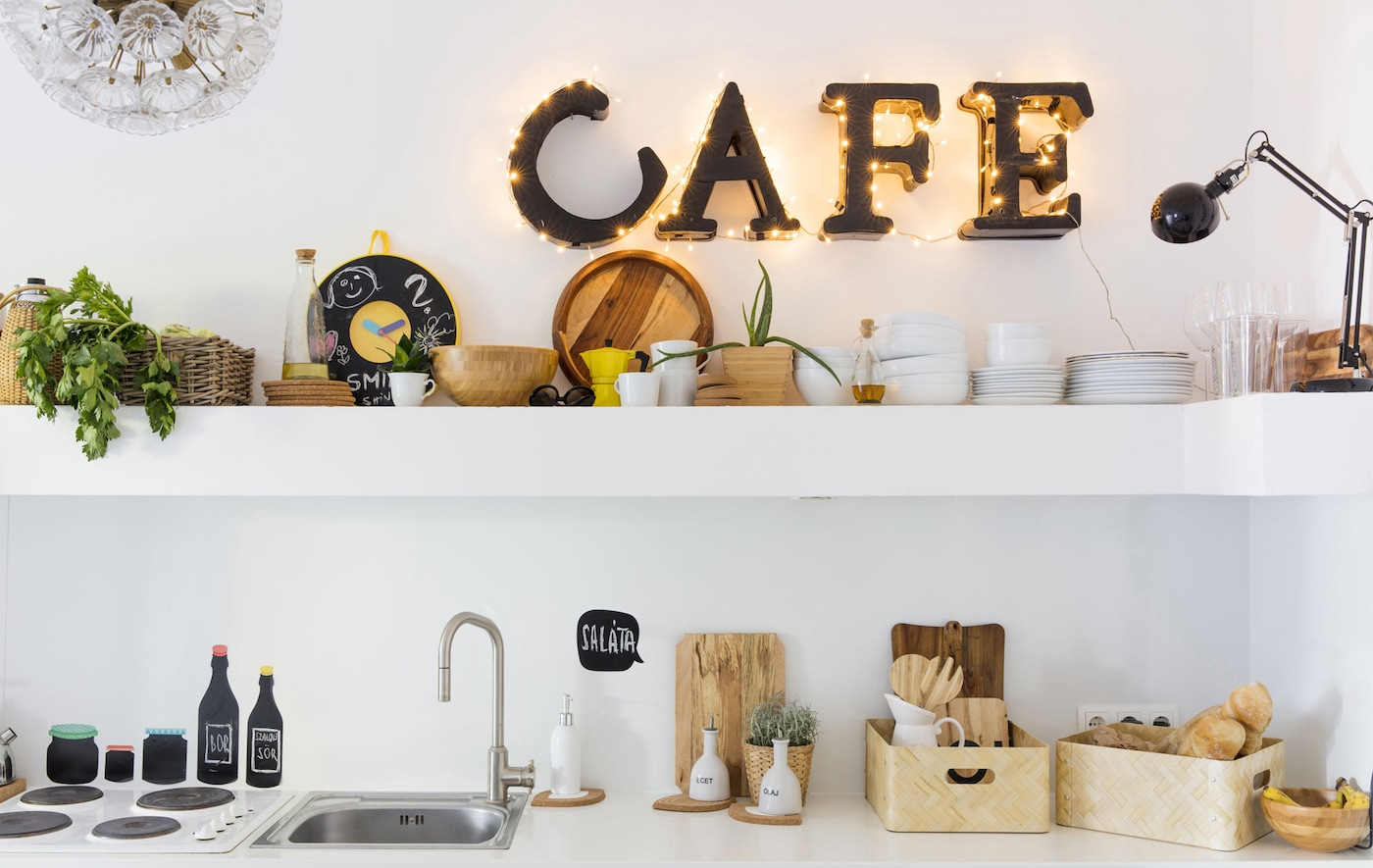 """Illuminated letters that spell out """"café"""" on the wall on a long shelf and the counter and sink of this white kitchen."""