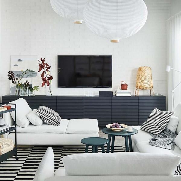 Ilmava olohuone, jossa on suuri, vaalea SÖDERHAMN-sohva, SÖDERHAMN-lepotuoli ja pitkä BESTÅ-lipasto STOCKVIKEN-ovilla.