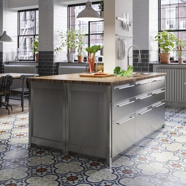 Îlot de cuisine avec plan de travail en chêne/plaqué et faces de tiroir en acier inoxydable. Rhubarbes hachées sur le plan de travail.