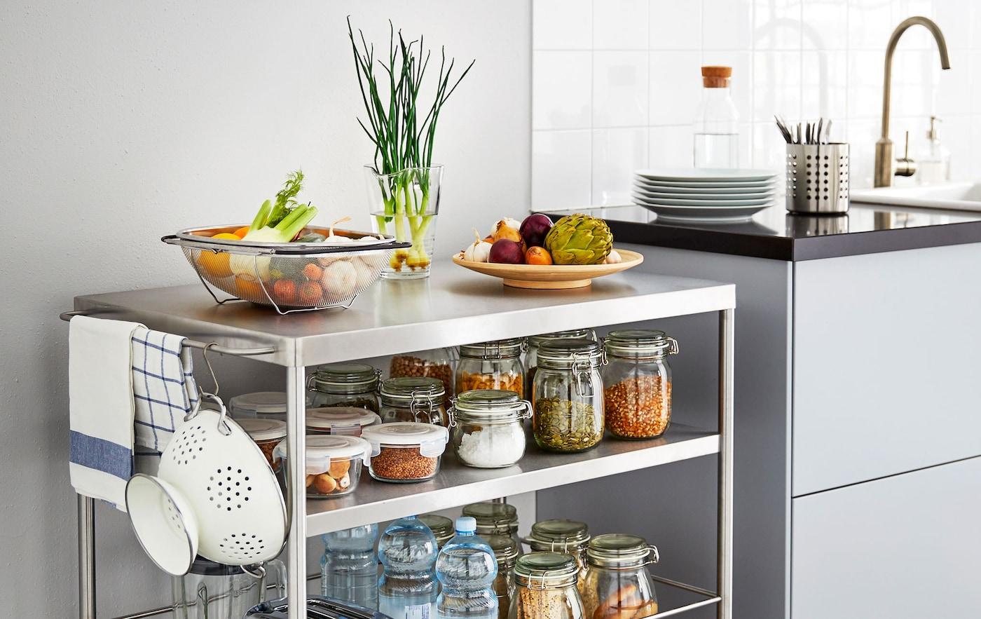 Îlot de cuisine métallique sur roulettes rempli de bocaux d'ingrédients, à côté d'un plan de travail.