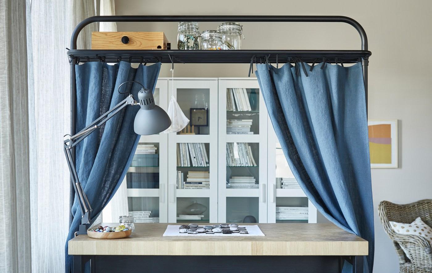 Îlot de cuisine placé dans un salon et équipé de rideaux bleus