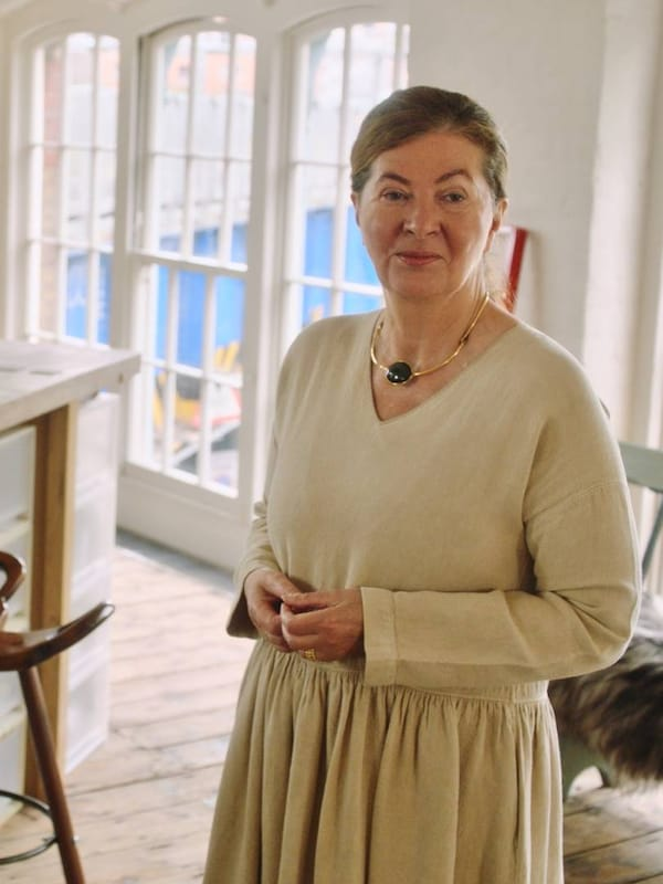 Ilse Crawford in a white room, wearing a beige dress and looking into the camera.