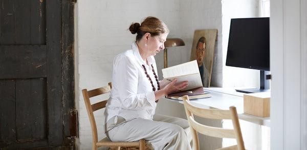 Ilse Crawford sitzt am Schreibtisch und liest ein Buch.