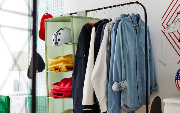 Image of a black clothes rail with shirts and a green organiser hanging from it