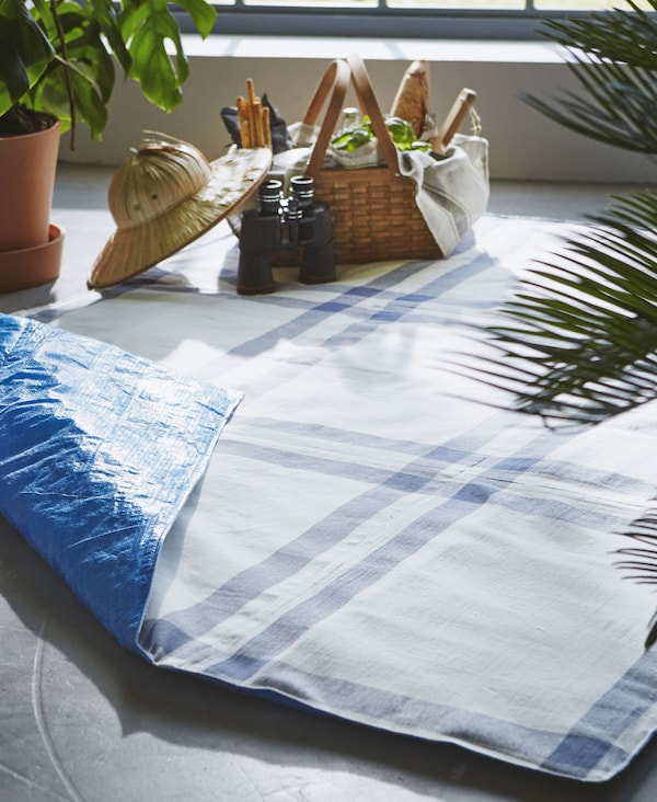 Image of a blue picnic blanket made from FRAKTA blue bags and tea towels laying on the floor