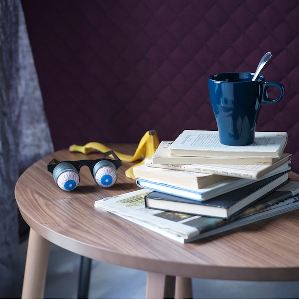 Image of a small side table with a stack of books and a mug.