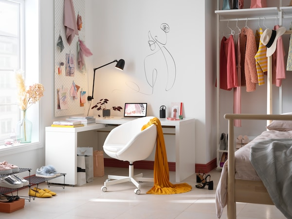 Image of a teenager's room, decorated in pastel pink and white tones, with a pretty desk, a light wooden bed frame and an open wardrobe. On the wall, there's a drawing of a woman, next to a pegboard. Natural light shines through the window creating an inviting atmosphere.