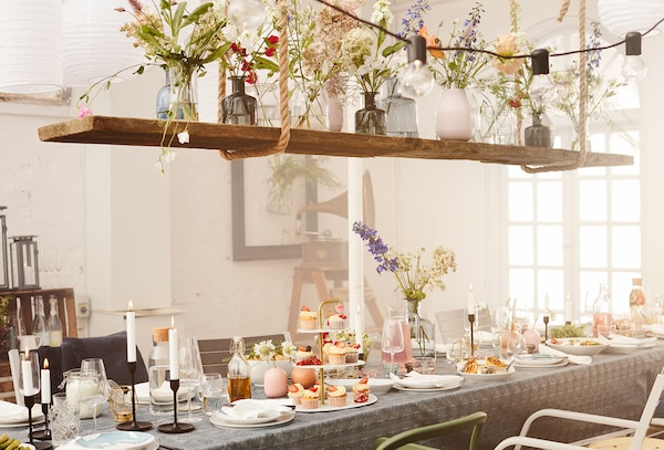 Image of a whimsical dining room decorated with flowers and string lights above a table spread with a dainty Mother's Day feast.