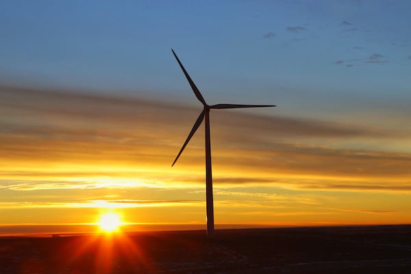 Image of a wind turbine in silhouette against a sunset.