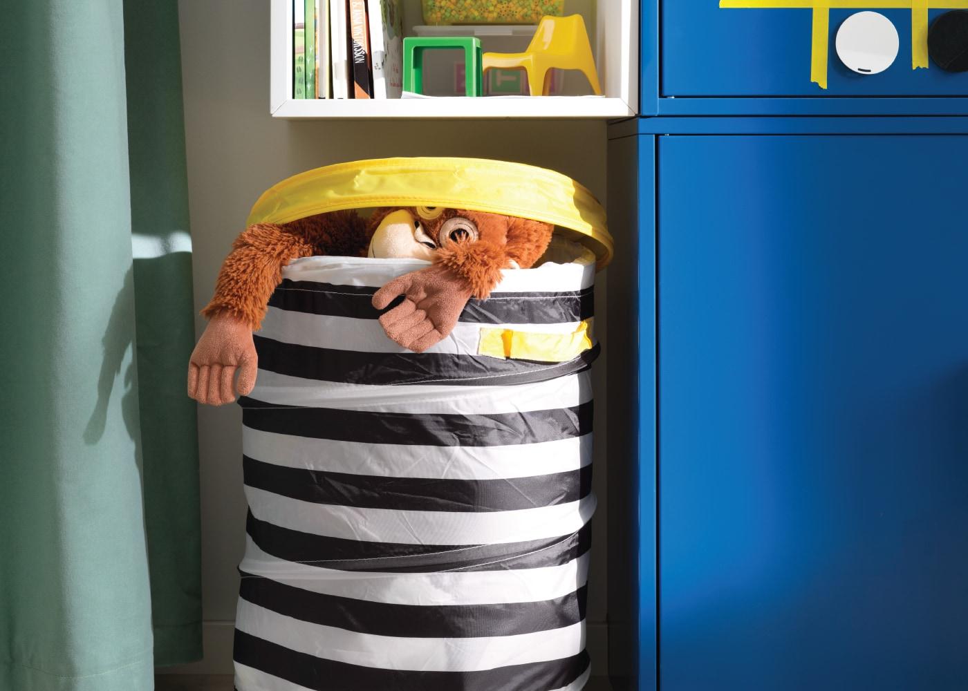 Imagem de um cesto com tampa com um peluche orangotango dentro.