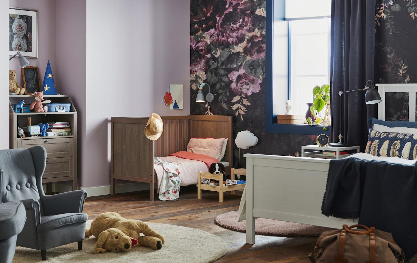 Imagem de um quarto com cama de casal, berço e brinquedos de criança.