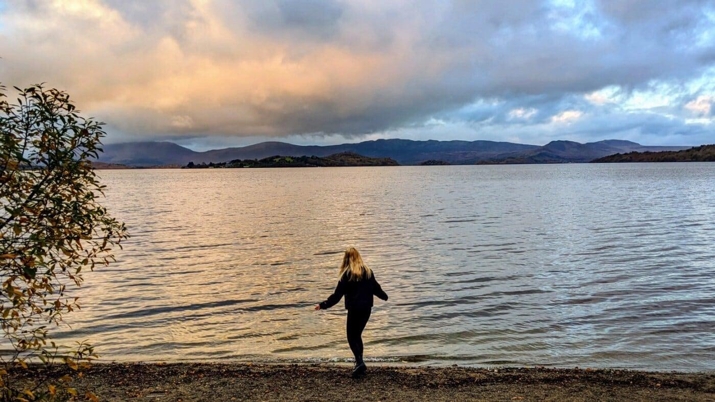 immagine di una donna che cammina sulla riva di un lago. Sullo sfondo ci sono delle montagne e delle nuvole.