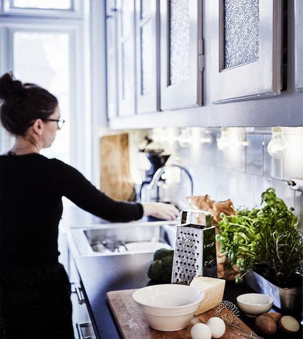إمرأة تقف أمام حوض المطبخ.