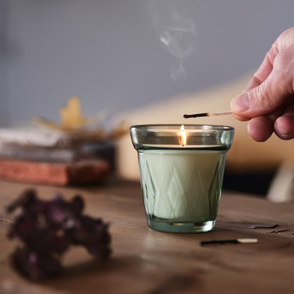 In a living room, a person's hand uses a match to light a morning dew-scented VÄLDOFT candle which is set on a coffee table.