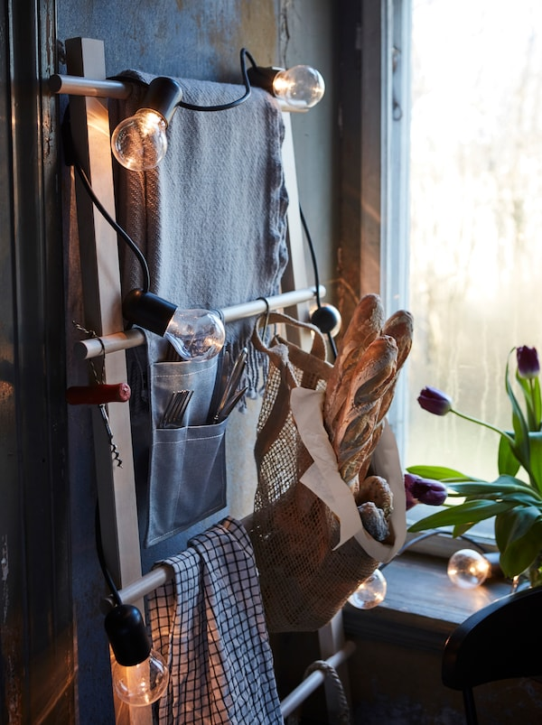 In a rustic room, a light chain decorates a towel stand that's being used as a clever, space-saving storage solution.