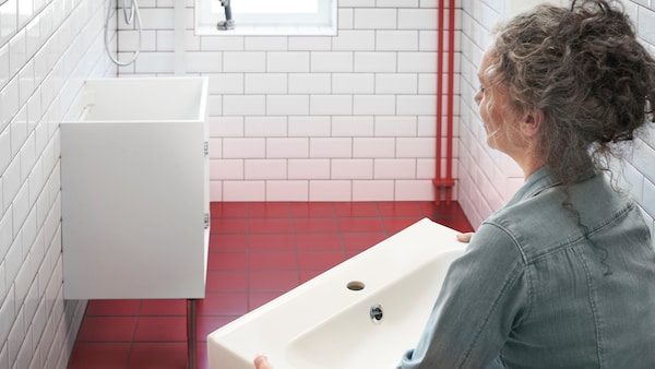 In a white and red tiled bathroom, a woman holds a white wash basin and looks at a white base cabinet fixed to the wall.
