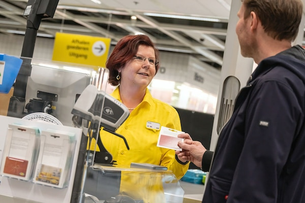 In an IKEA store, a customer is buying an IKEA Gift Card from a cashier.