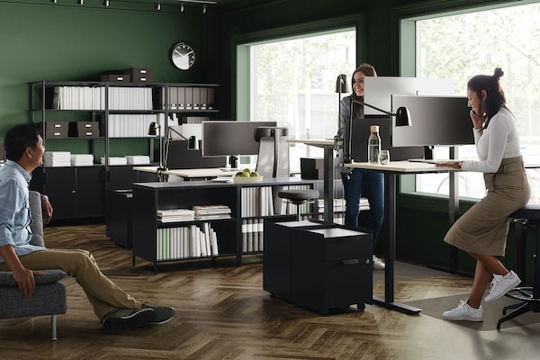 In an office with green walls are three employees having a conversation. One employee is seated while two are on their workstations.