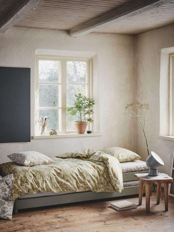 În colțul unei încăperi bine luminate cu plafon din lemn, o canapea extensibilă comodă cu o lenjerie de pat JUNIMAGNOLIA.