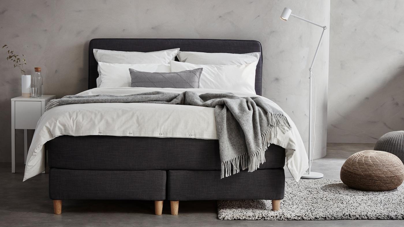 In einem Schlafzimmer in Hellgrau steht ein dunkelgraues DUNVIK Boxspringbett mit weißer Bettwäsche. Neben dem Bett befindet sich eine weiße NYMÅNE Stand-/Leseleuchte und zwei Bodenkissen.