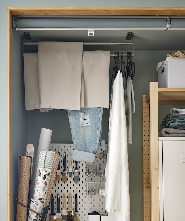 In einer Raumnische ist in Regalen, an einer Lochplatte und an einer an die Decke befestigten Handtuchstange unterschiedlicher Hobbybedarf untergebracht.