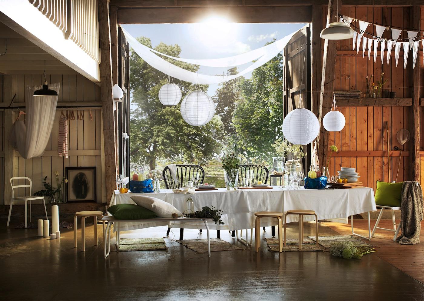 In einer Scheune steht eine lange Tafel mit LINNMON Tischen & weißer Tischdecke für die Sommerparty.