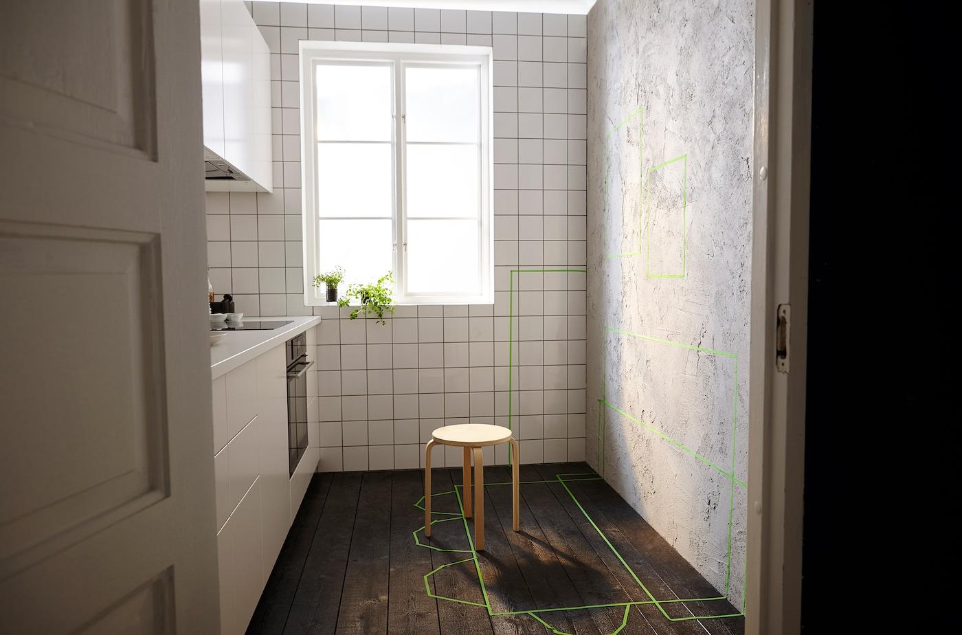 In einer schmalen Küche sieht man grünes Klebeband, das die Platzierung von Möbeln zeigt.
