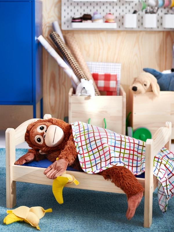 in Spielzeugaffe liegt in einem Puppenbettchen von IKEA.