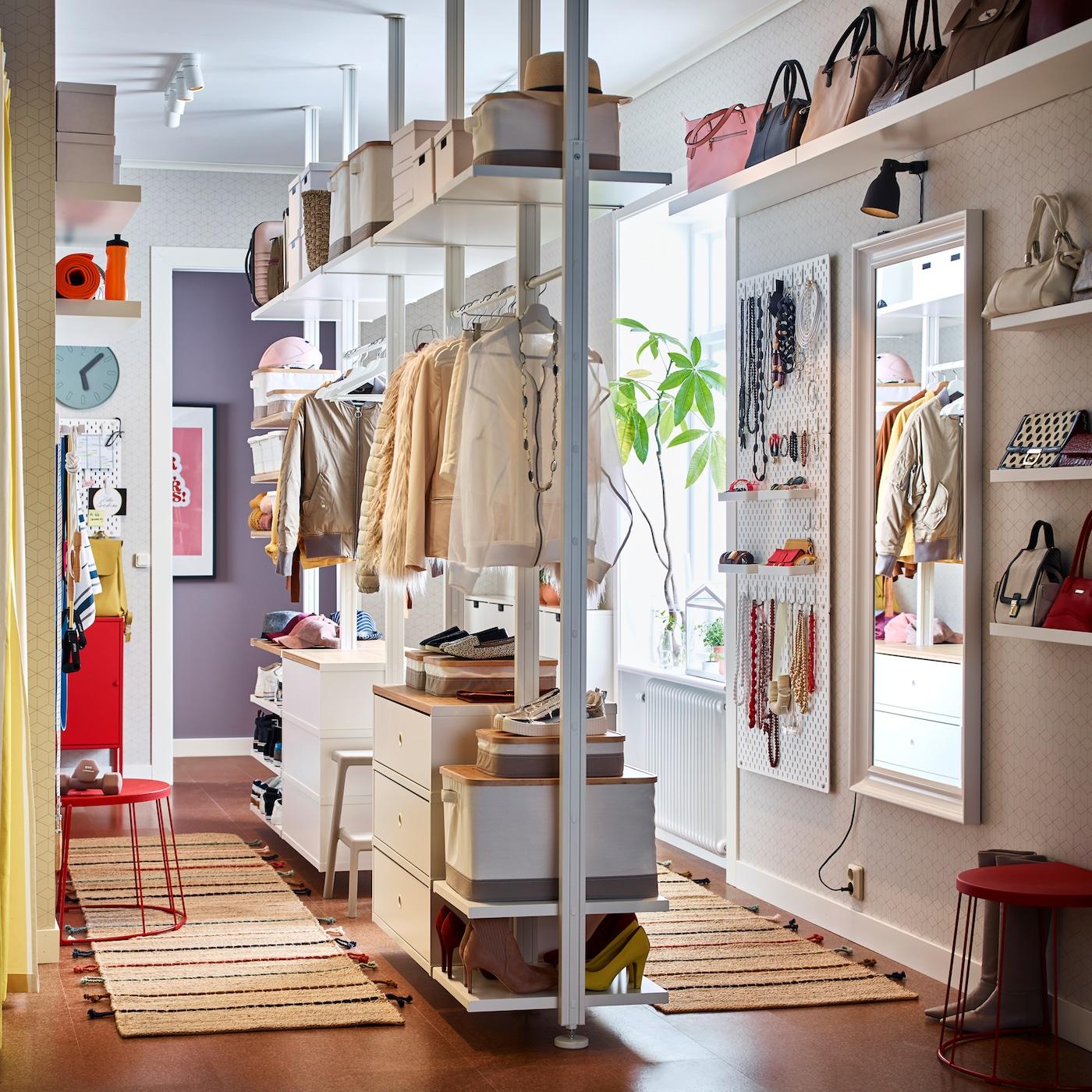 In una cabina armadio stretta è stata creata una combinazione a giorno ELVARLI bianca, completa di bastoni appendiabiti e cassetti. Questa combinazione è al centro della cabina armadio, così è possibile sfruttare le pareti con mensole e altre soluzioni per organizzare vestiti e accessori – IKEA