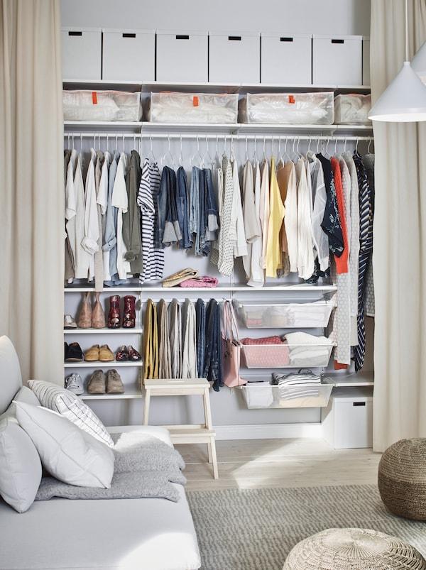 Încăpere unde un perete este amenajat cu perdele până la podea trase care dezvăluie o garderobă organizată de-l lungul întregului perete.