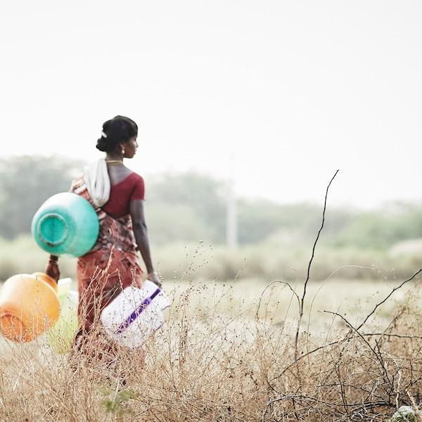 インドの社会起業家団体に属する女性の職人が野原を歩いています。