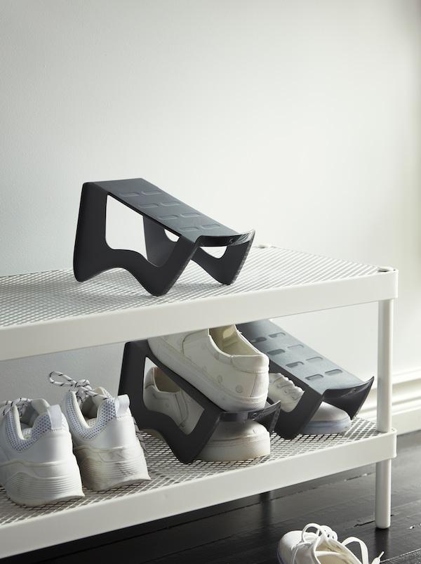 Ingresso con rastrelliera per scarpe bianca con ripiani in rete e tre portascarpe compatti MURVEL in plastica grigia.
