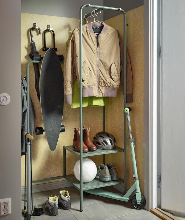 Ingresso con stand appendiabiti NIKKEBY con abiti appesi, scarpe e un casco. Attorno allo stand vari accessori per le attività all'aperto - IKEA