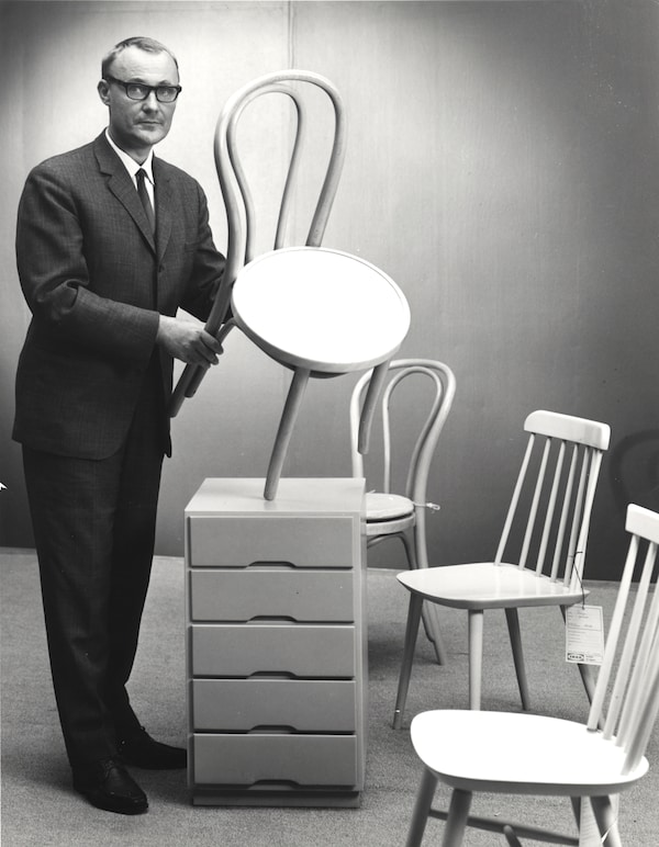 Ingvar Kamprad en el inicio de su empresa IKEA, mostrando productos icónicos como las sillas escandinavas clásicas y veladores también del mismo estilo de diseño. Foto en blanco y negro.
