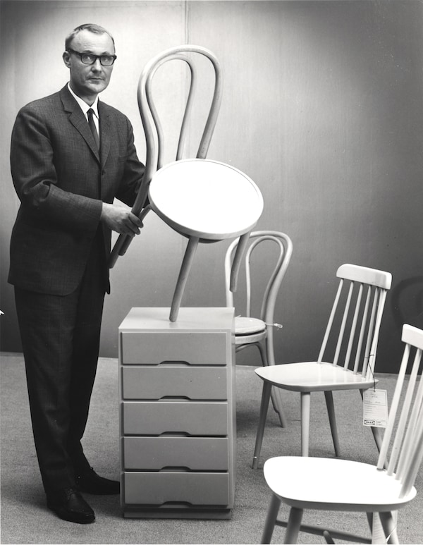 Ingvar Kamprad holding a dining chair next to other chairs, in a black and white photo.