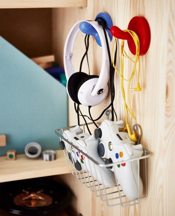 Innenseite eines IVAR Schrankes mit KROKIG Wandhaken in Bunt, an denen Kopfhörer hängen, darunter ein Korb mit Spielkonsolen-Controllern