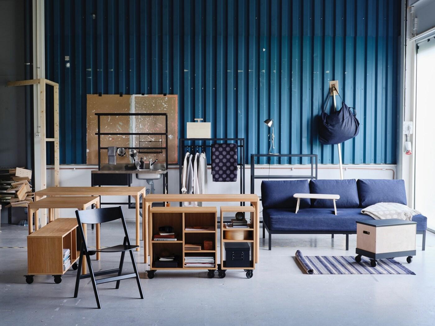 Inrett rum med RÅVAROR kollektion där flera möbler står i mitten av ett rum framför en blå vägg