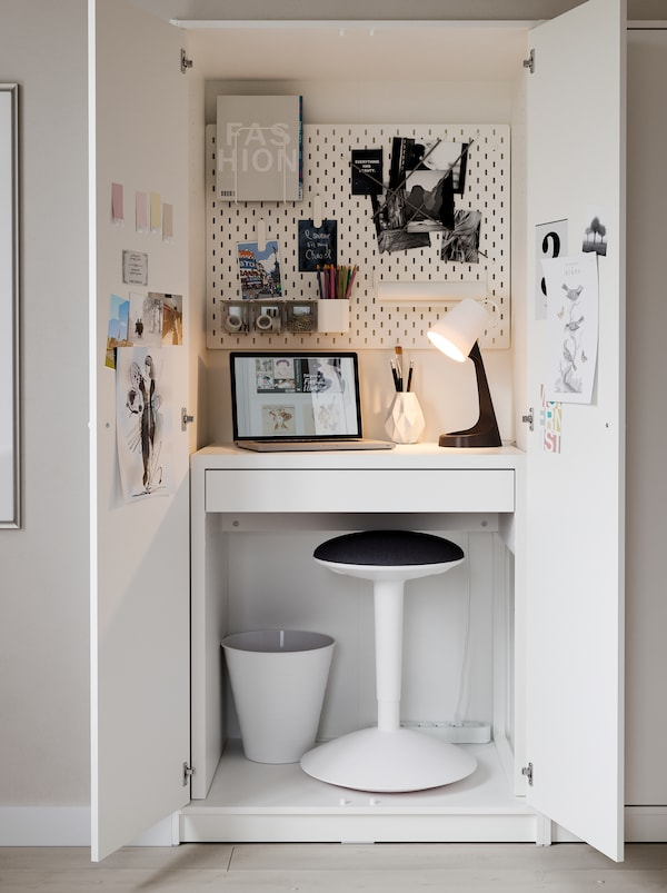 Inside a KLEPPSTAD wardrobe, a MICKE desk, a NILSERIK standing support, a lamp and a pegboard form a very compact workspace.