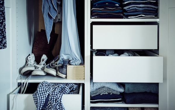 Inside of a PAX wardrobe with shelves, drawers and hanging space, filled with clothes and shoes.