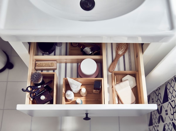 Inside the top drawer of a wash-stand, filled with an IKEA DRAGAN bamboo 4-piece bathroom set, holding bathroom accessories.