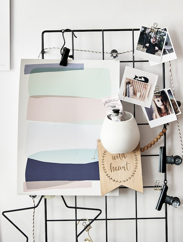 Inspiration and photos clipped to a wire rack on a wall.