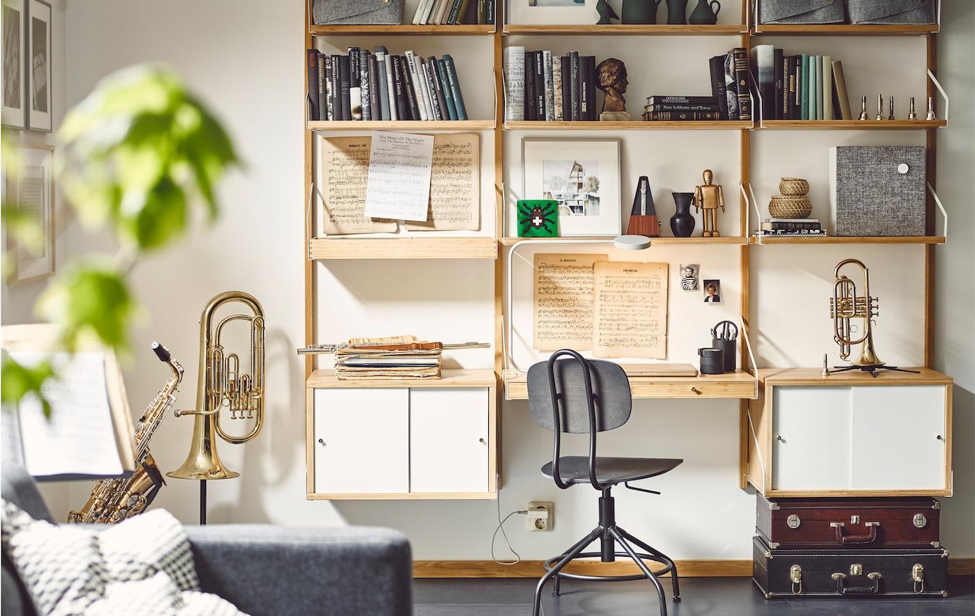 Instruments de musique, musique et livres disposés sur un rangement mural avec module bureau et armoires.
