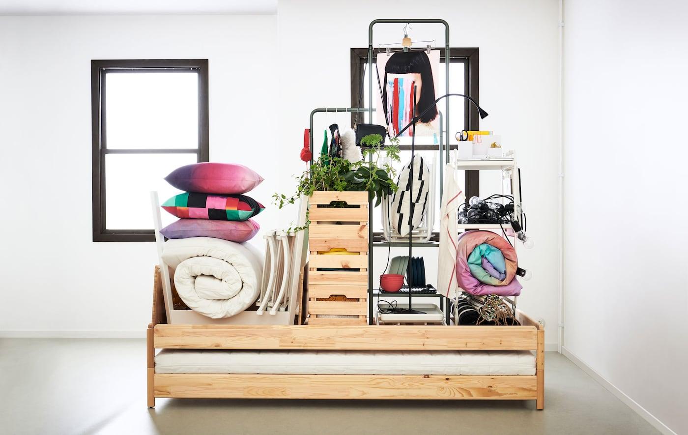 Интерьер комнаты или квартиры с неокрашенными стенами; по центру стоит кровать, на которой сложена вся мебель и принадлежности для маленького дома.