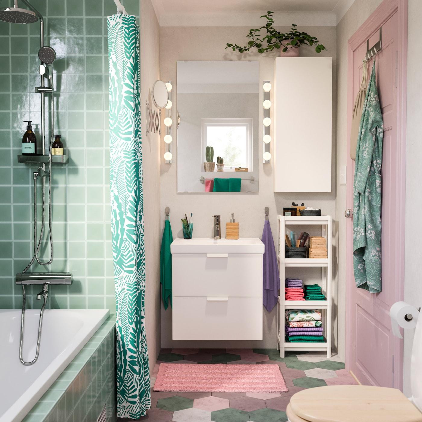 Интерьер ванной в розовых и бирюзовых тонах: раковина и навесной шкаф белого цвета, розовый коврик для ванной и бирюзовая штора для ванной.