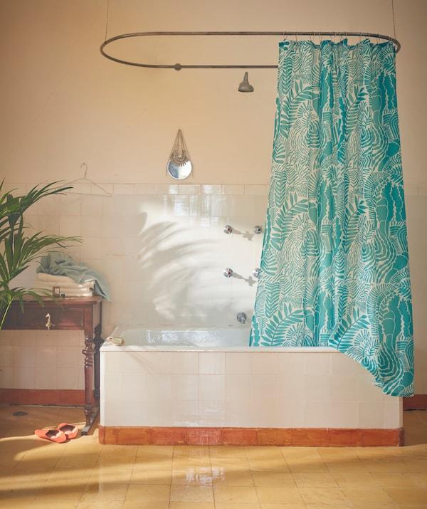 Interiér kúpeľne s vaňou s kúpeľňovým závesom GATKAMOMILL zaveseným na tyči s oblým tvarom.