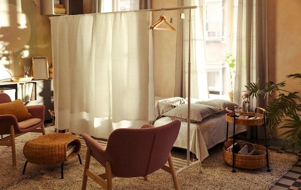Interiér obývacej izby so širokou posteľou umiestnenou za paravánom vyrobeným z vešiaka RIGGA a posteľných plachiet VÅRELD.