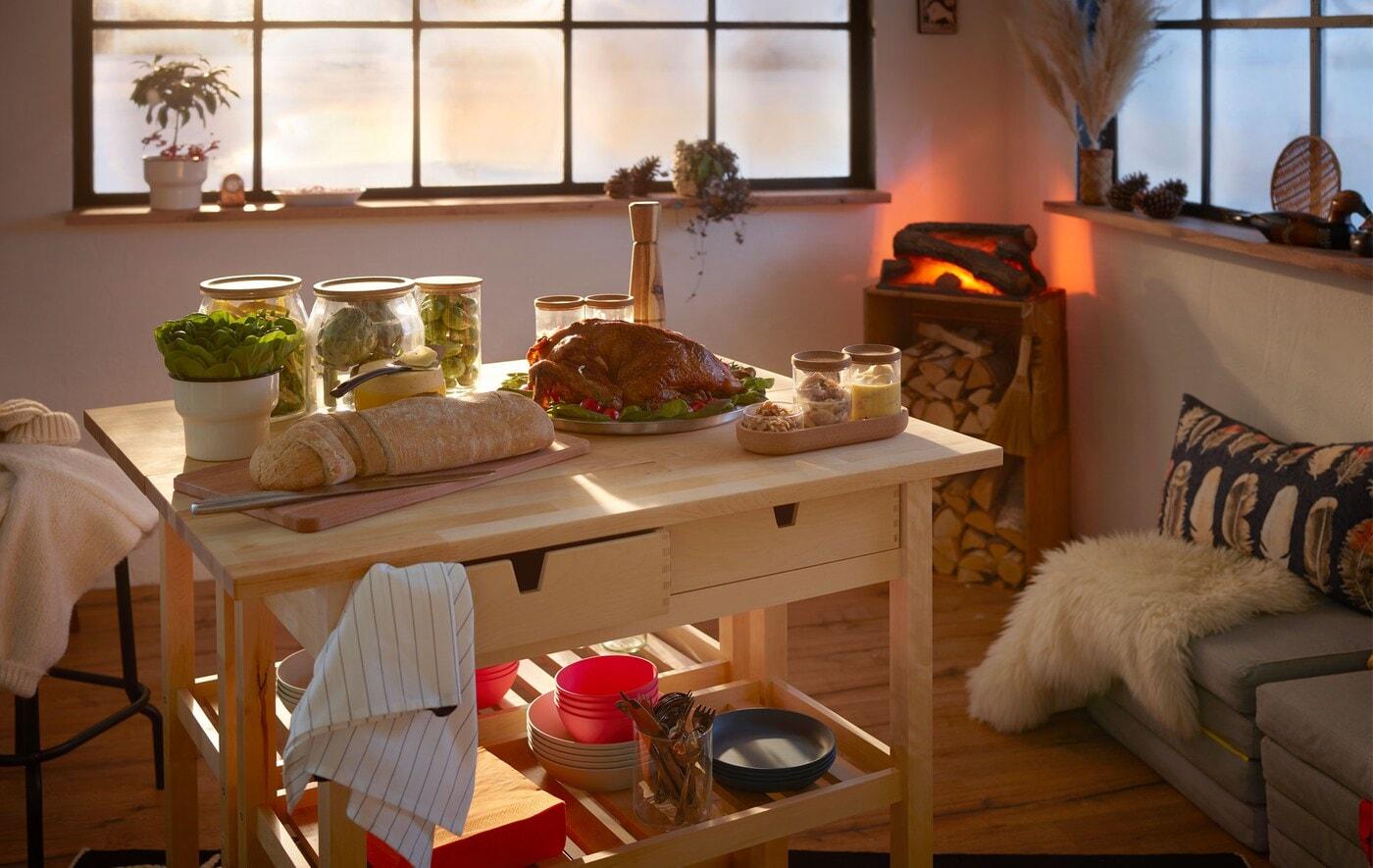 Interiér ve stylu srubu, na dřevěném vozíku spousta jídla, vzadu je krb a velká okna