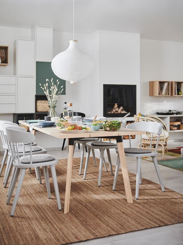 Intérieur combinant salon et salle à manger avec un foyer, un rangement mural, une table à manger YPPERLIG et des chaises OMTÄNKSAM.